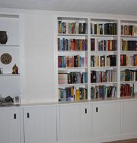 Boekenkast op maat om pilaar heen gebouwd